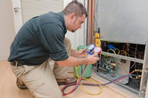 HVAC Service technician repairing air conditioning unit.
